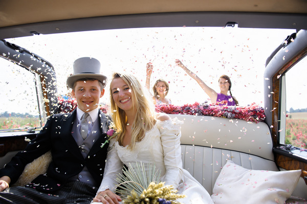 Wedding Guests Throwing Confetti from Shropshire Petals Over Couple in Car