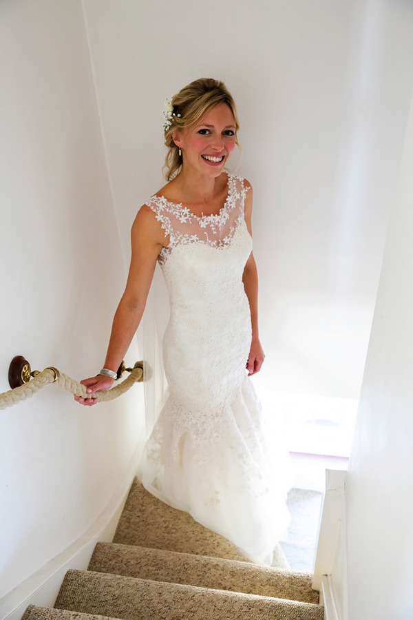 Bride standing on stairs in Elizabeth Van Stone wedding dress