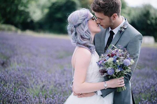 Bride with purple hair about to kiss groom in field of lavender - Picture by Lucie Watson Photography