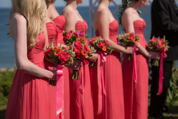 Bridesmaids in pink dresses holding colourful bouquets