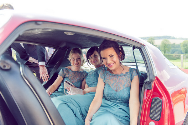 Bridesmaids in back of Pontiac Firebird