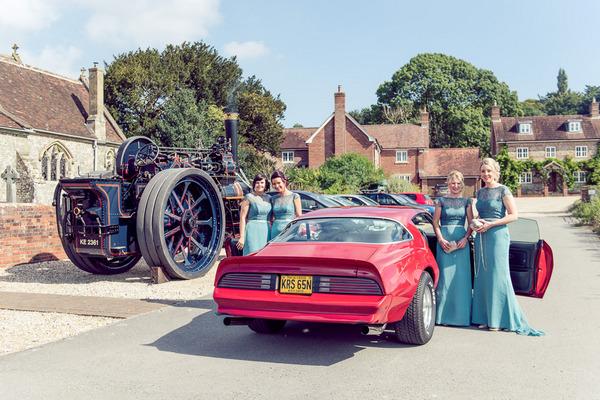 Bridesmaids standing by Pontiac Firebird
