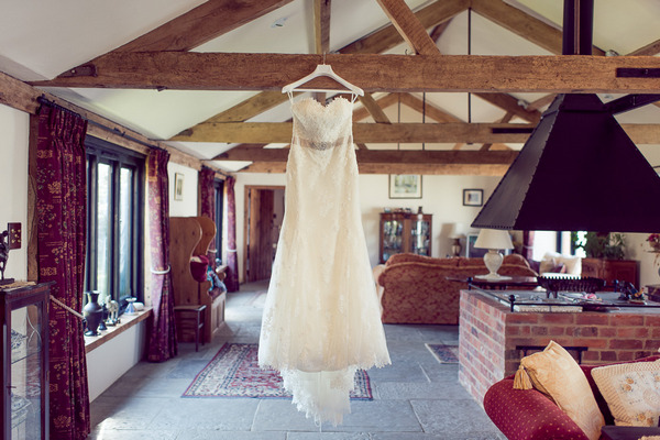 Wedding dress hanging from ceiling beam