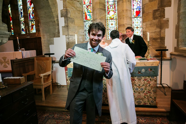 Groom holding marriage certificate