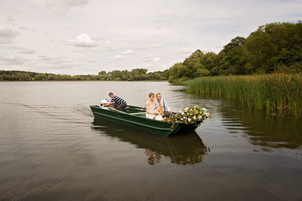 Bride and groom in boat on lake