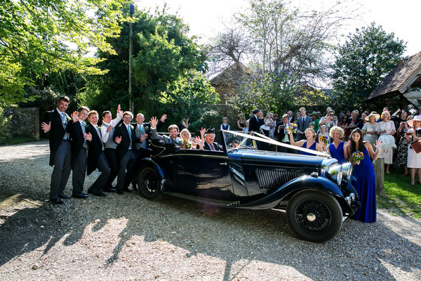 Bride and groom in vintage Bentley wedding car