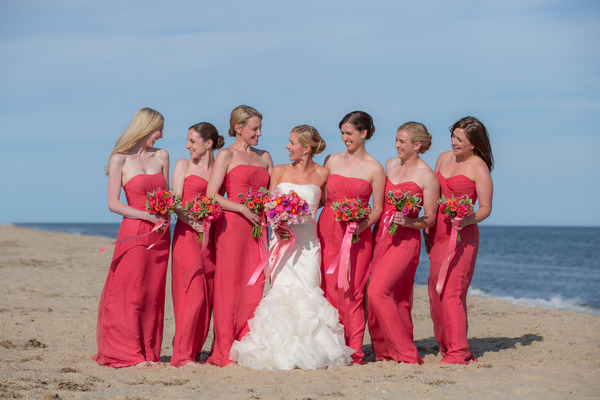 Bride and bridesmaids in pink dresses on beach