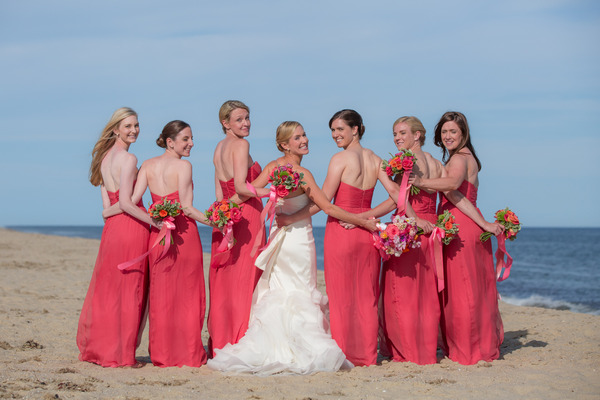 Bride and bridesmaids standing in row with back to camera