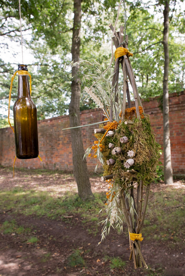Beer bottles and rustic flowers hanging from tree