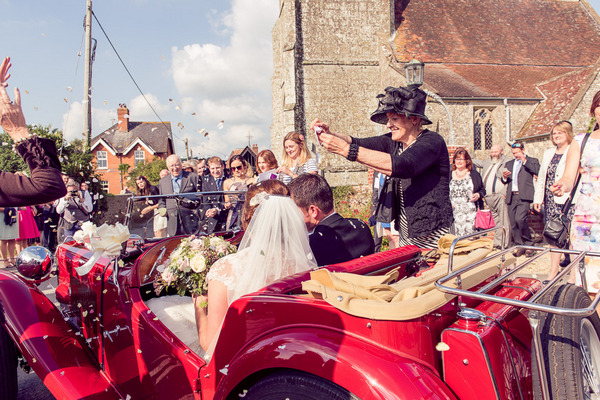 Lady throwing confetti over bride and groom in vintage MG TC 1947 wedding car
