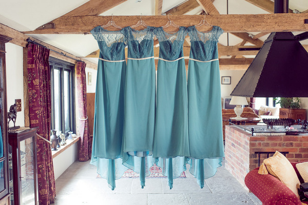 Light blue bridesmaid dresses hanging from ceiling beam