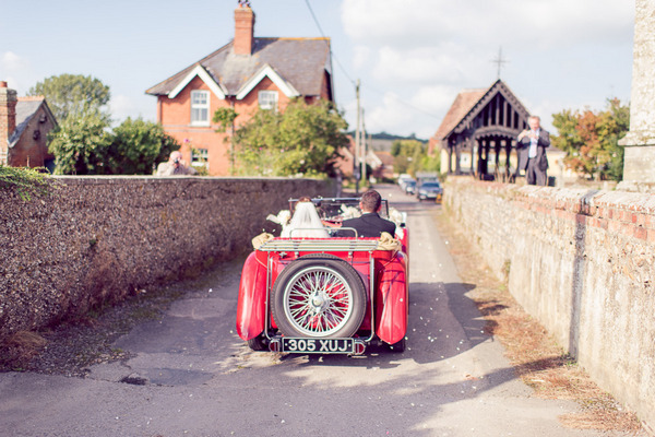 Bride and groom driving to reception in vintage MG TC 1947 wedding car