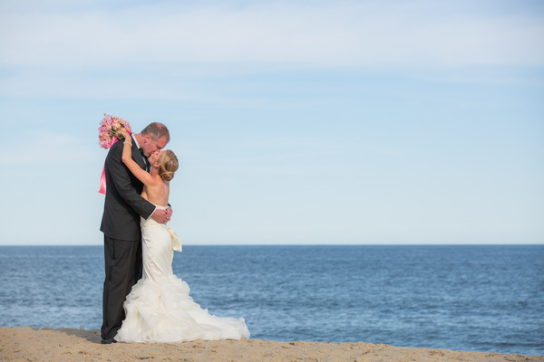 Bride and groom kiss by sea on Nantucket Island