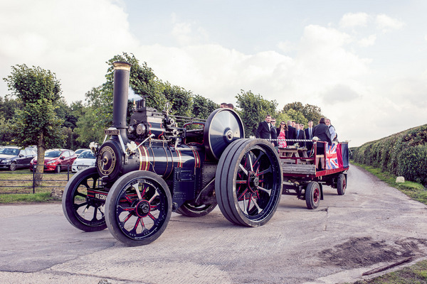 Wedding guests arriving at reception on vintage farm steam engine
