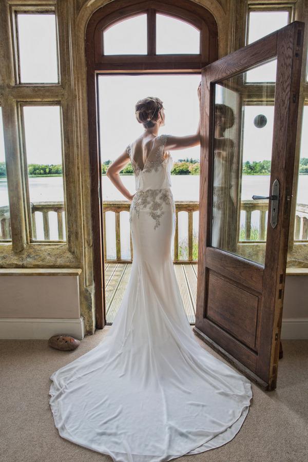 Bride standing in doorway overlooking lake