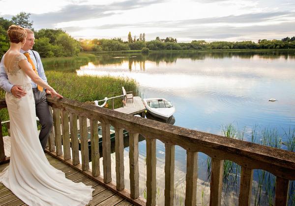 Bride on balcony overlooking lake
