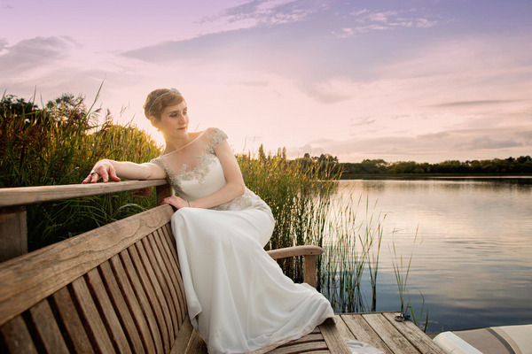 Bride on bench by lake