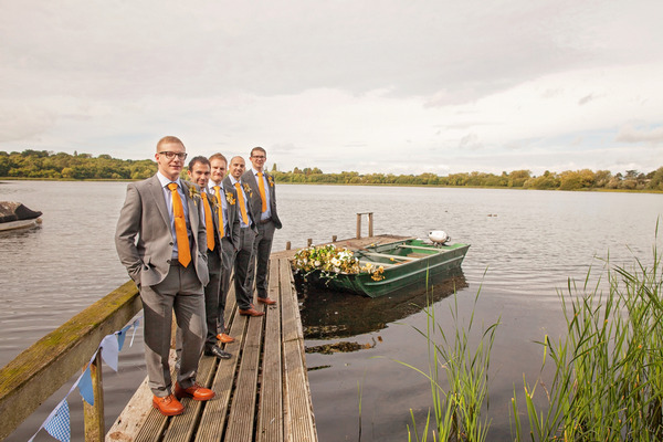 Row of groomsmen by lake