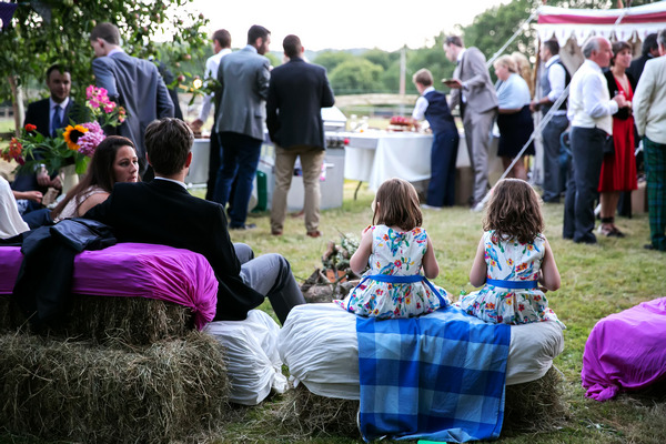 Wedding guests sitting on hay bales