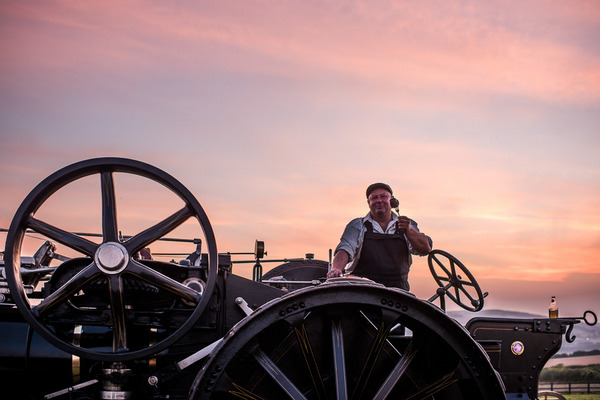 Man on vintage farm steam engine