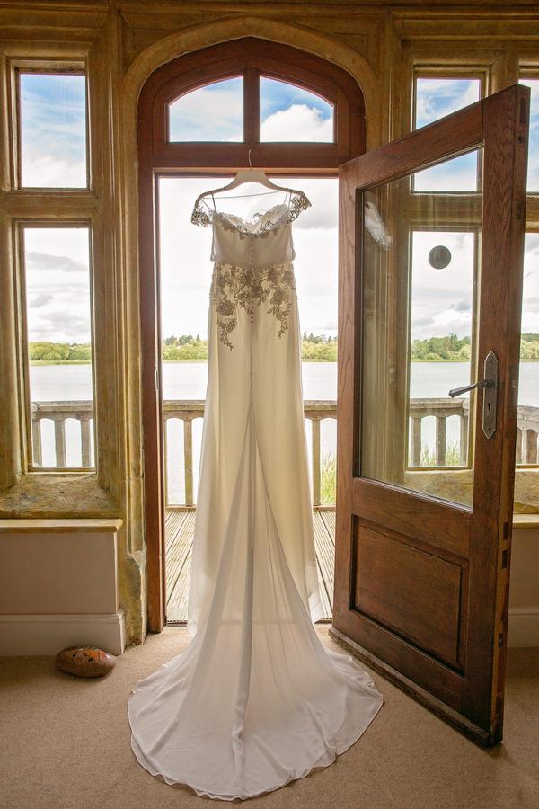 Harlem wedding dress by Enzoani, hanging in doorway