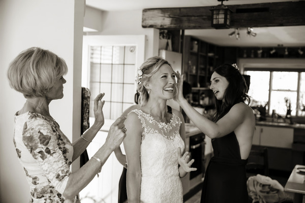 Bridesmaids and mother helping bride get ready