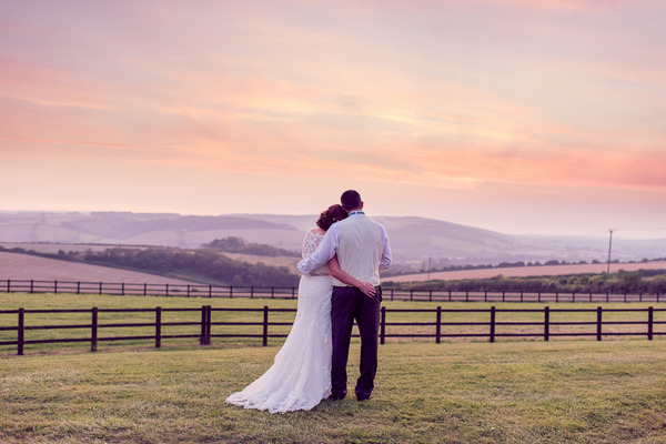 Bride and groom looking at view of Dorset countryside at sunset