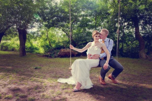 Bride and groom sitting on rope swing
