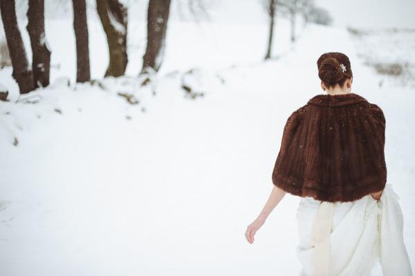 Bride with fur shrug walking in snow