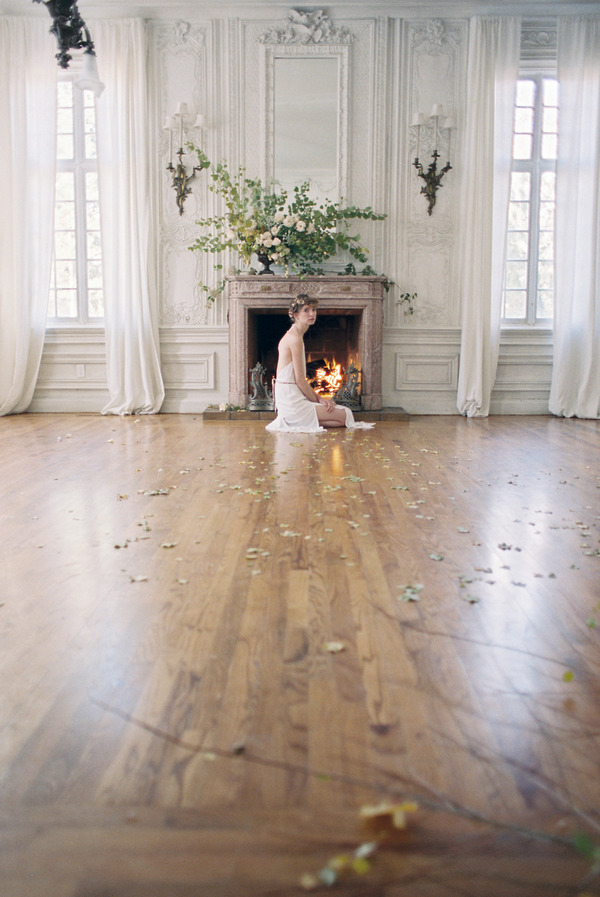 Bride kneeling next to fireplace