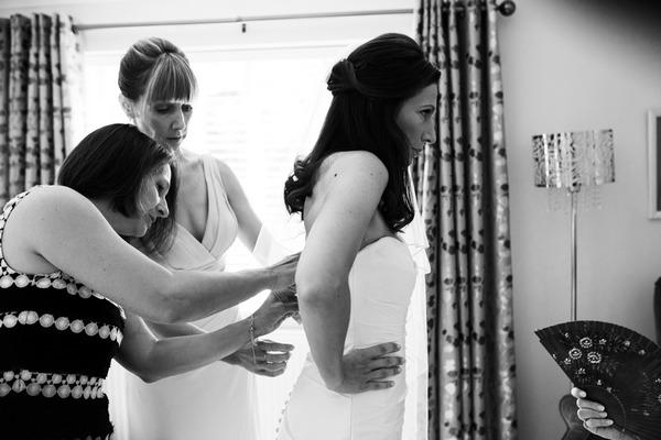 Bridesmaids doing up bride's dress