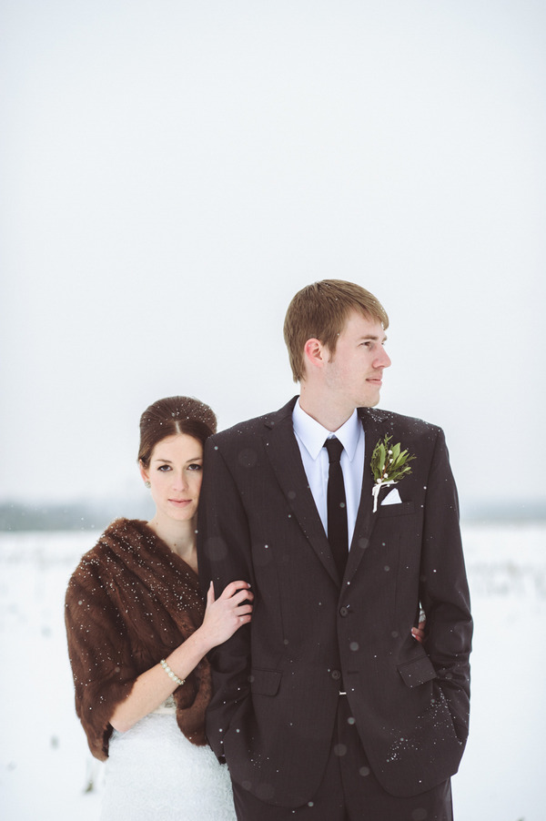 Bride standing with groom in snow