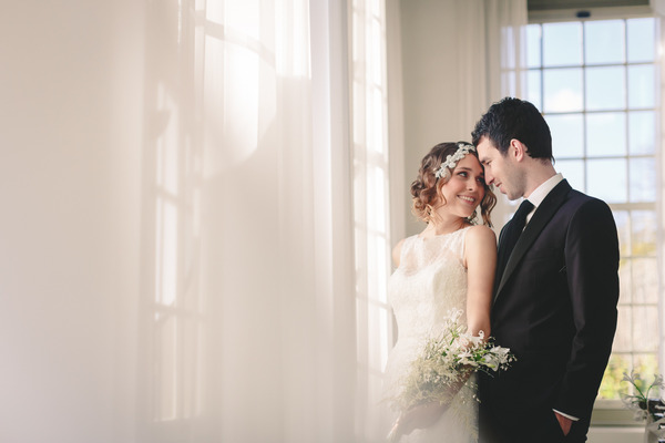 Bride and groom standing by window