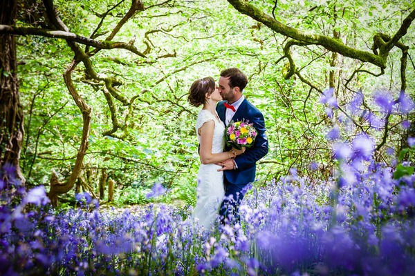 Bride and groom kissing under trees behind purple flowers - Picture by Alexa Poppe Wedding Photography