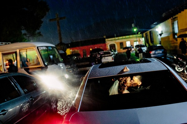 Bride and groom kissing in back of car in car park - Picture by Caroline Studios