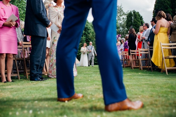 Picture of father walking bride down aisle taken through groom's legs - Picture by Marianne Chua Photography