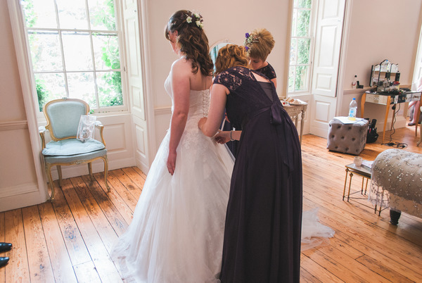 Bridesmaid helping bride with wedding dress
