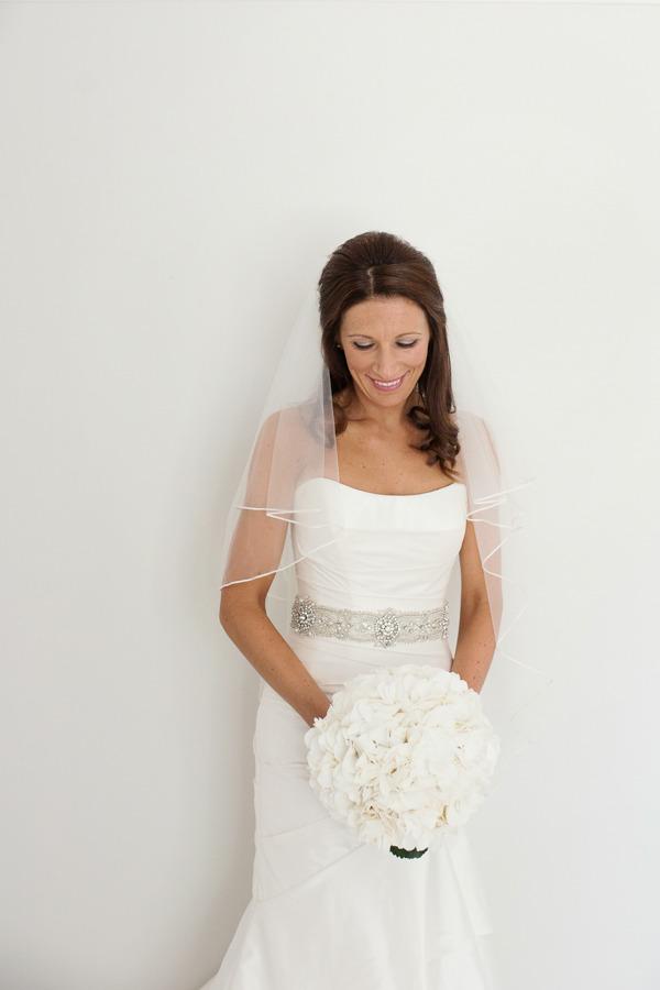 Bride with belt holding bouquet