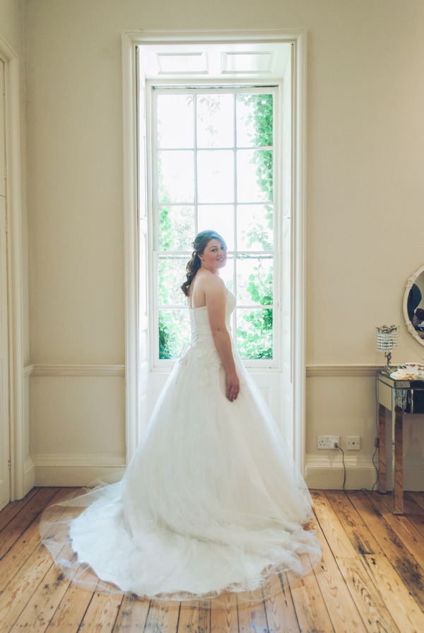 Bride standing in front of window