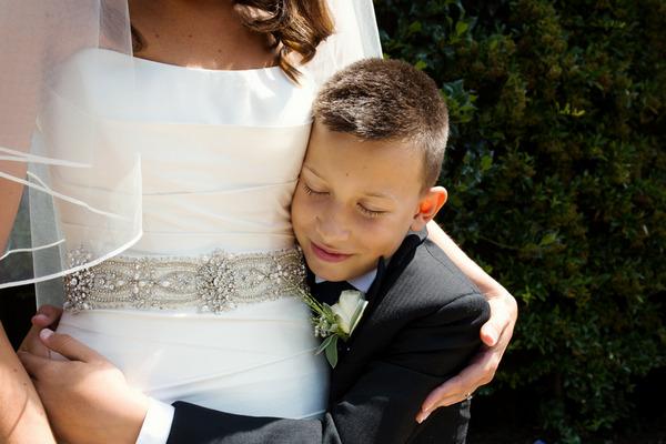 Boy hugging mum on her wedding day