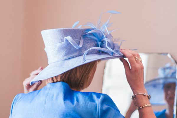 Bride's mother putting on hat