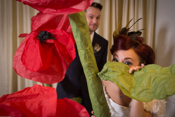 Bride and groom peering through large paper poppies