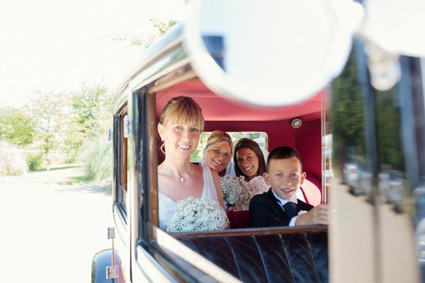 Bride, bridesmaids and pageboy in back of wedding car