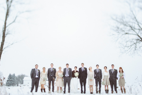 Wedding party standing in snow