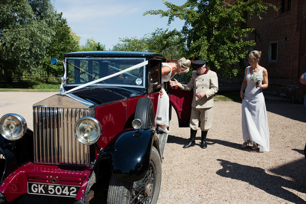 Bride getting out of classic wedding car