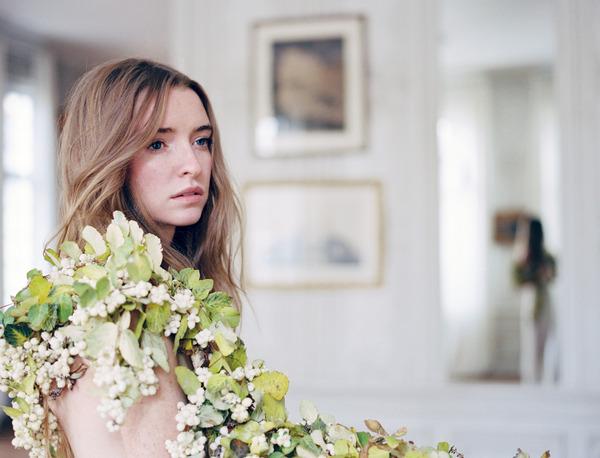 Bride with flower and leaf wreath over shoulder