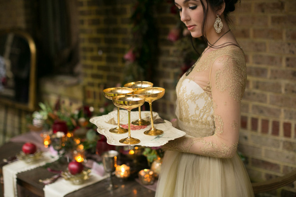 Bride holding tray of gold cups