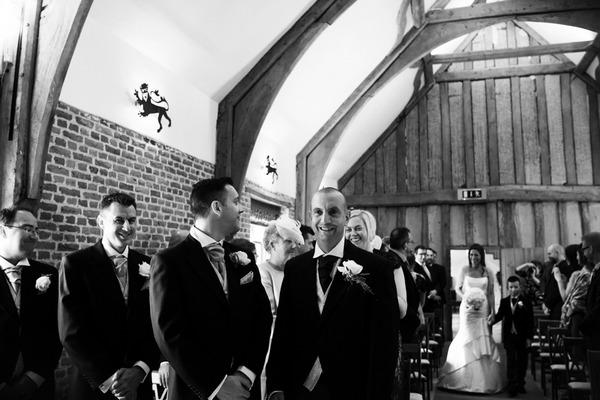 Groom standing at altar as bride walks down the aisle