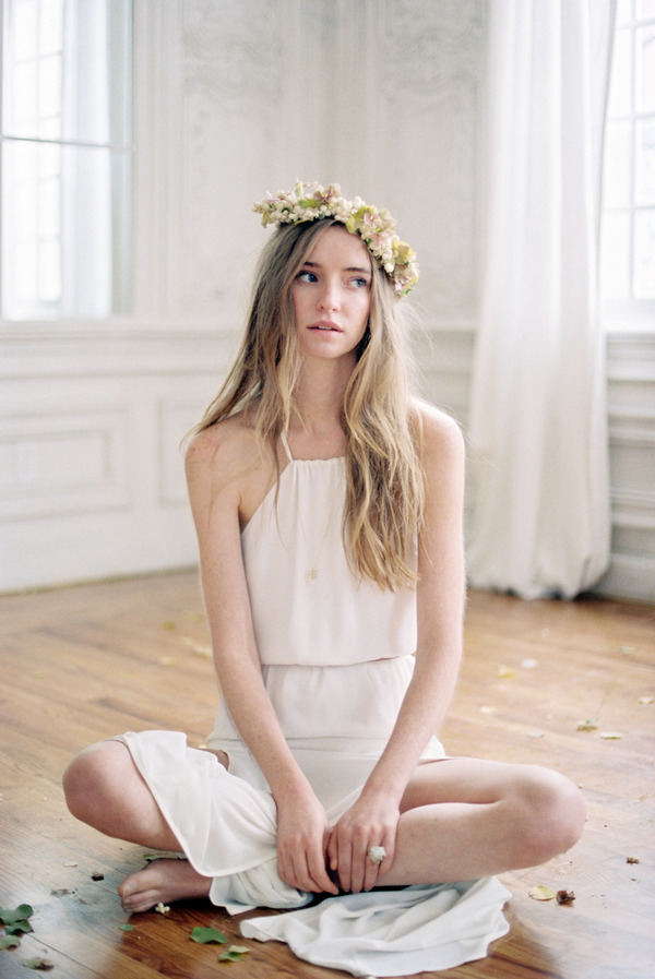 Bride with flower crown sitting with legs crossed