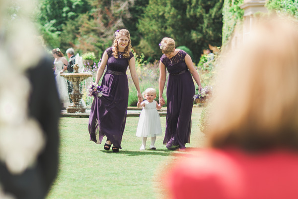 Bridesmaids leading flower girl down the aisle